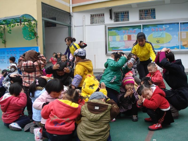 近期,中国云南盈江发生5.8级地震,日本发生震级强达9级的地震,并引发高达10米的海啸,对人类造成极大的毁灭性破坏。为帮助全园教师与幼儿在实践中运用所掌握的防震知识,提高面临突发事件时的应急能力,机关幼儿园领导小组针对防震逃生演练活动进行工作部署,并制定了详细方案。教师围绕地震、防震小知识等相关资料设计了一系列教学活动,让幼儿了解地震灾害和地震逃生技巧,同时于3月30日上午开展了防震逃生演练活动。 演练当日10点整,第一次地震报警铃声响起,各班教师指导孩子们迅速钻到课桌下或者是蹲在坚实的橱柜边和墙边以及